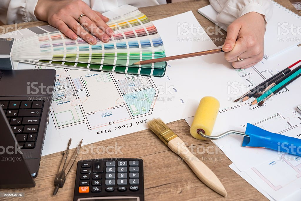 Architect sketching construction project with laptop, color palette, work tools stock photo