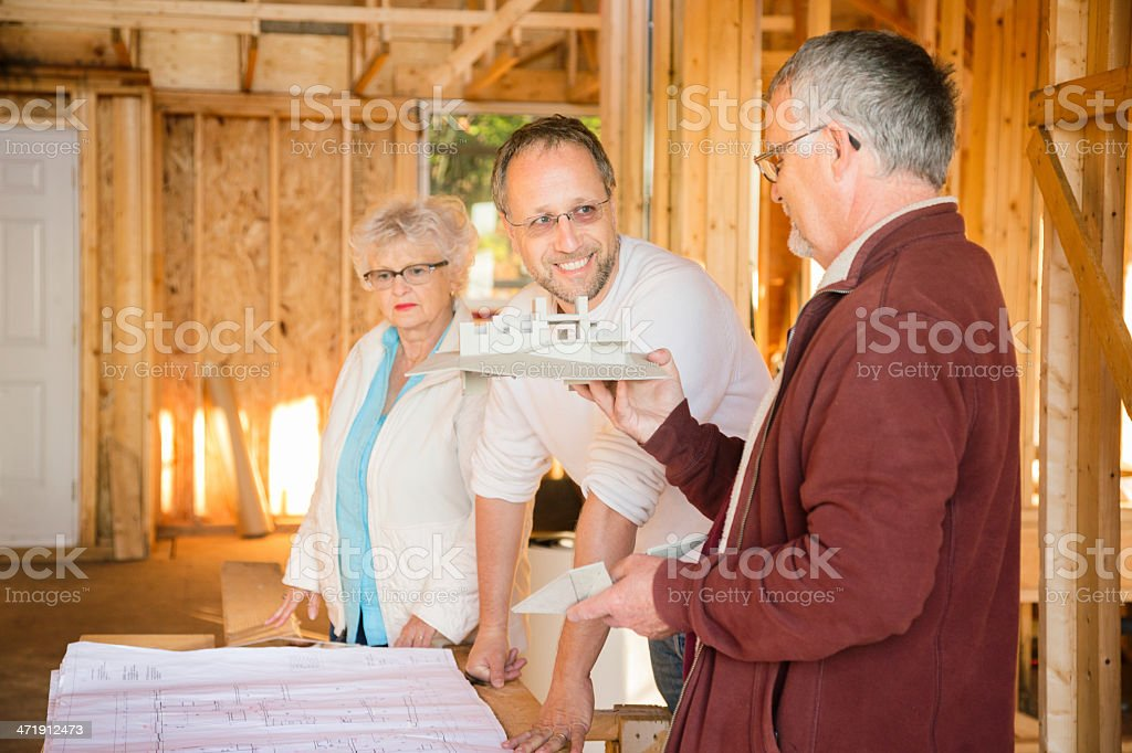 Architect smiles as customers look at plans and model royalty-free stock photo