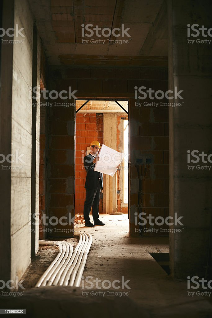 Architect standing in house under construction with building pla royalty-free stock photo