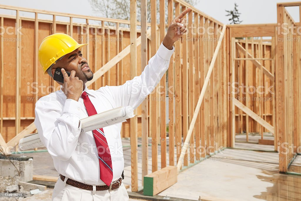 Architect Talking on Cell Phone with Plans royalty-free stock photo