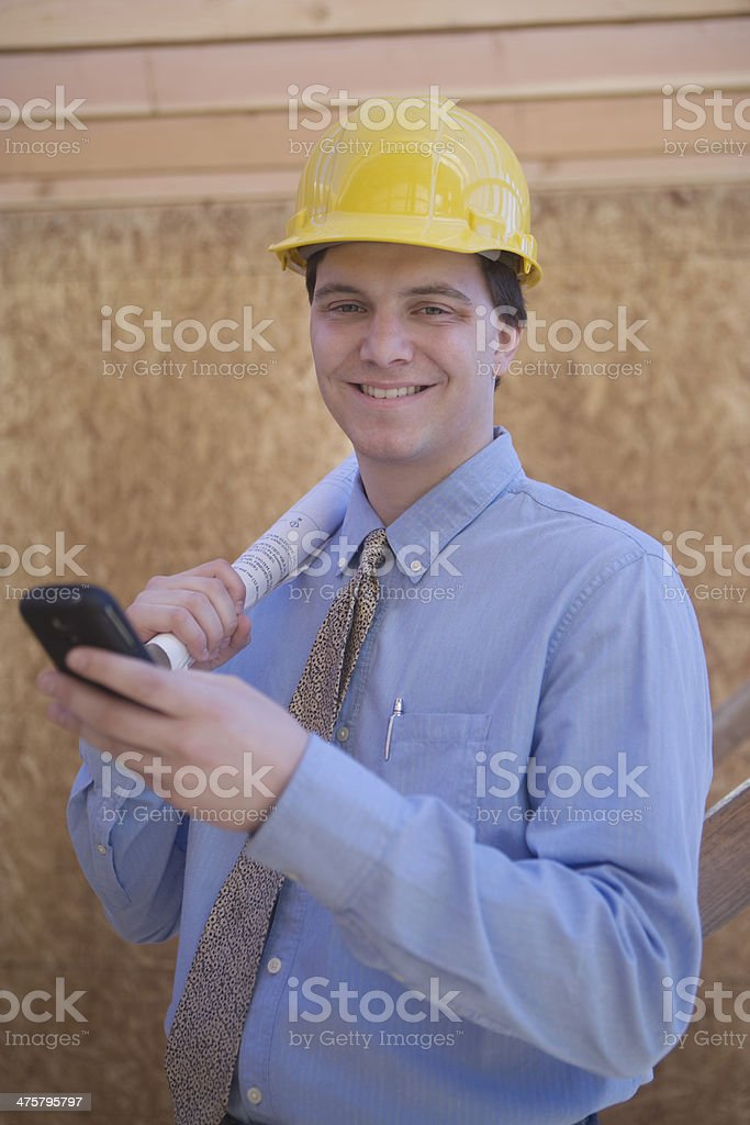 Architect Using Cell Phone With Blueprint At Site royalty-free stock photo