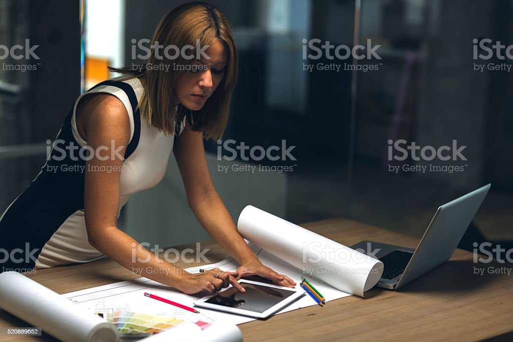 Architect using digital tablet late in her office. stock photo
