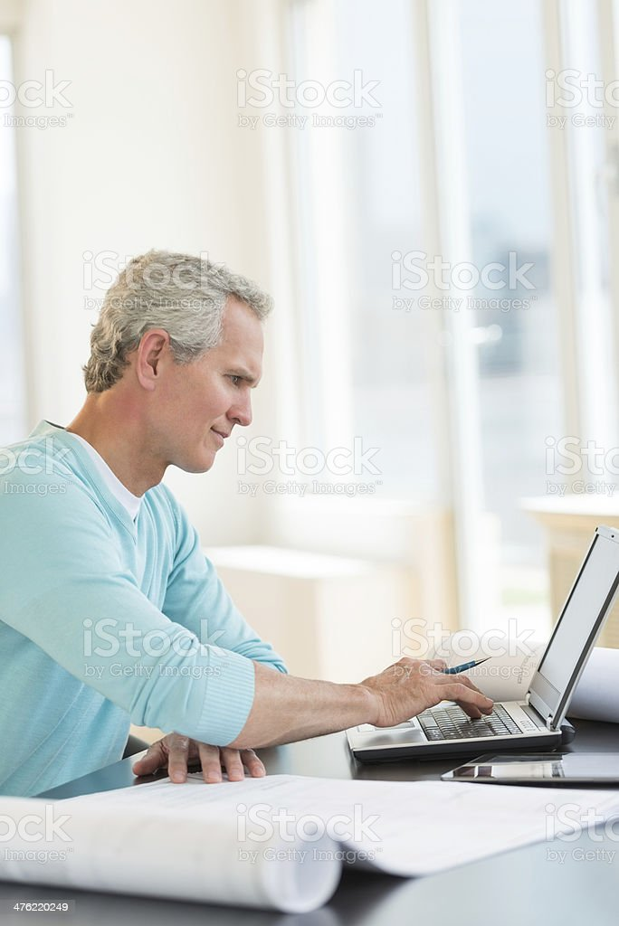 Architect Using Laptop At Desk stock photo