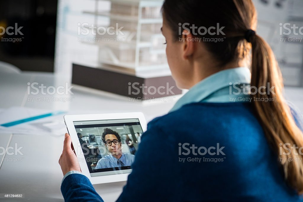 Architect video chatting with man on digital tablet stock photo