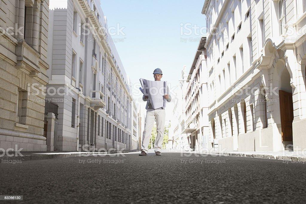 Architect with blueprints standing on urban street stock photo