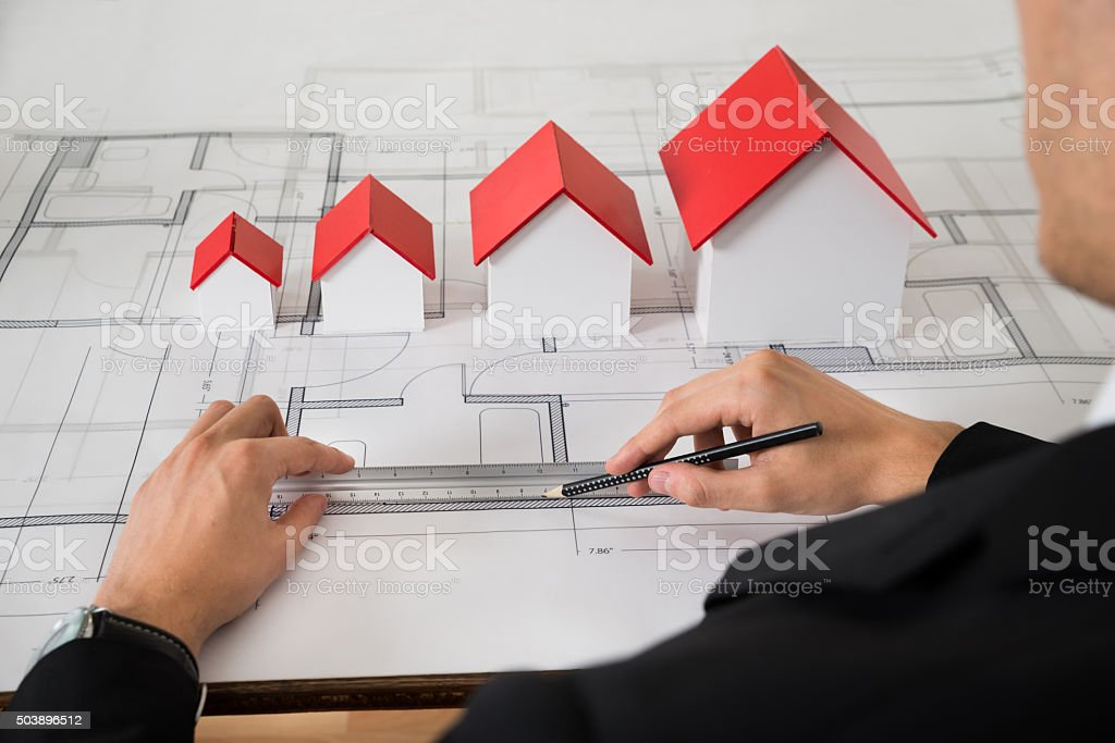 Architect With Different Size House Models On Blueprint stock photo