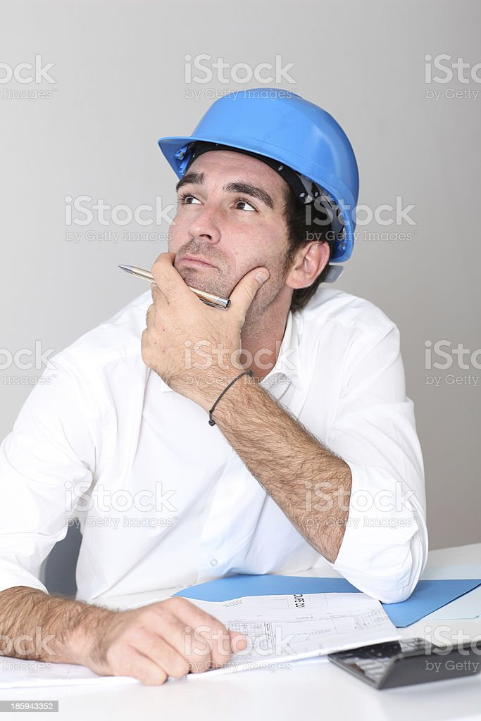 Architect with helmet sitting at desk royalty-free stock photo