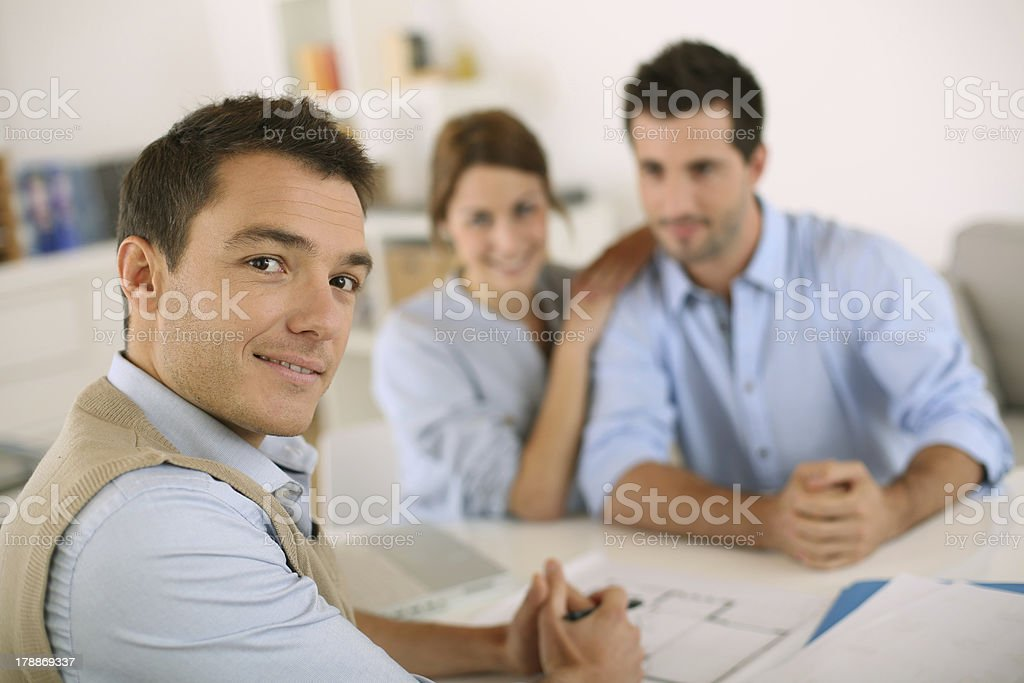 Architect with young couple in office royalty-free stock photo