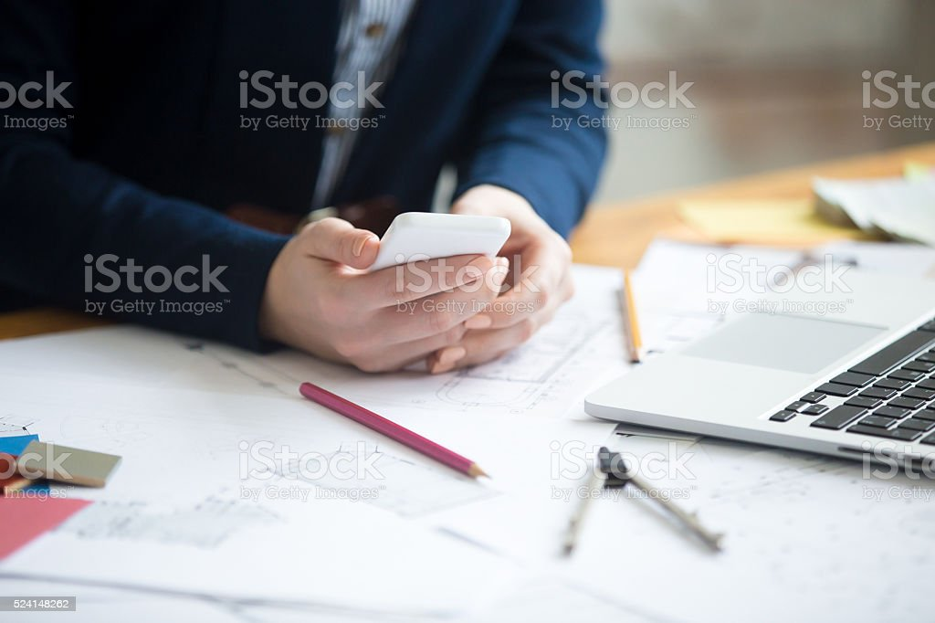 Architect woman using phone, close-up stock photo