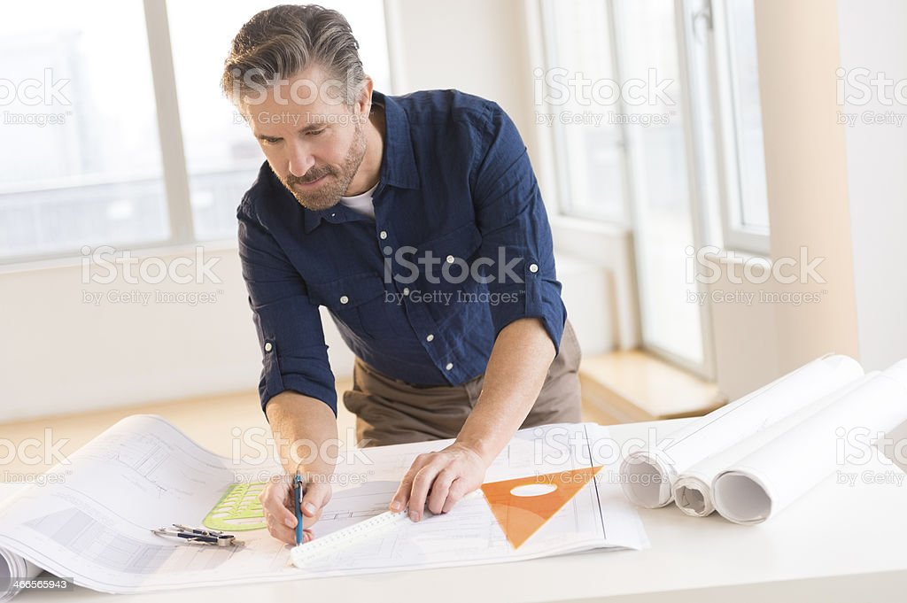 Architect Working On Blueprint At Office Desk stock photo