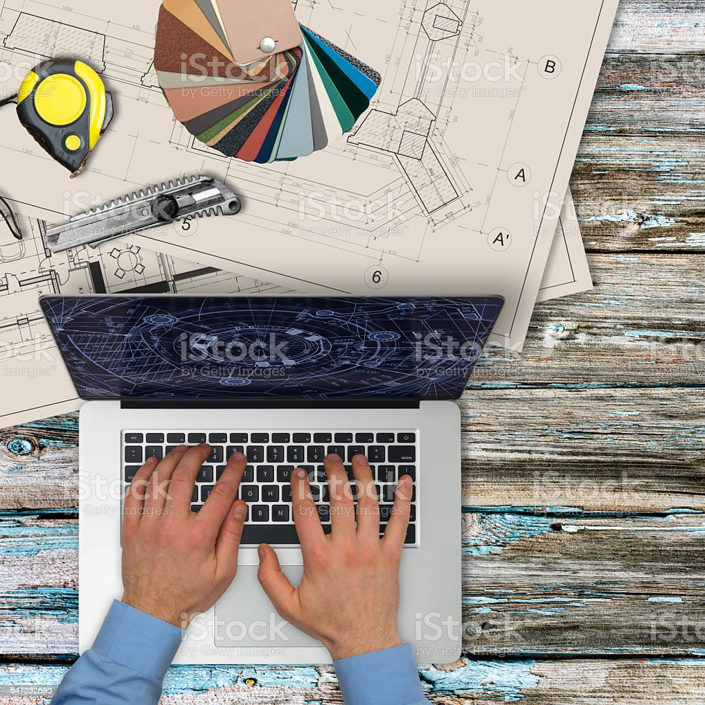 Architect working on laptop on wooden desk. stock photo