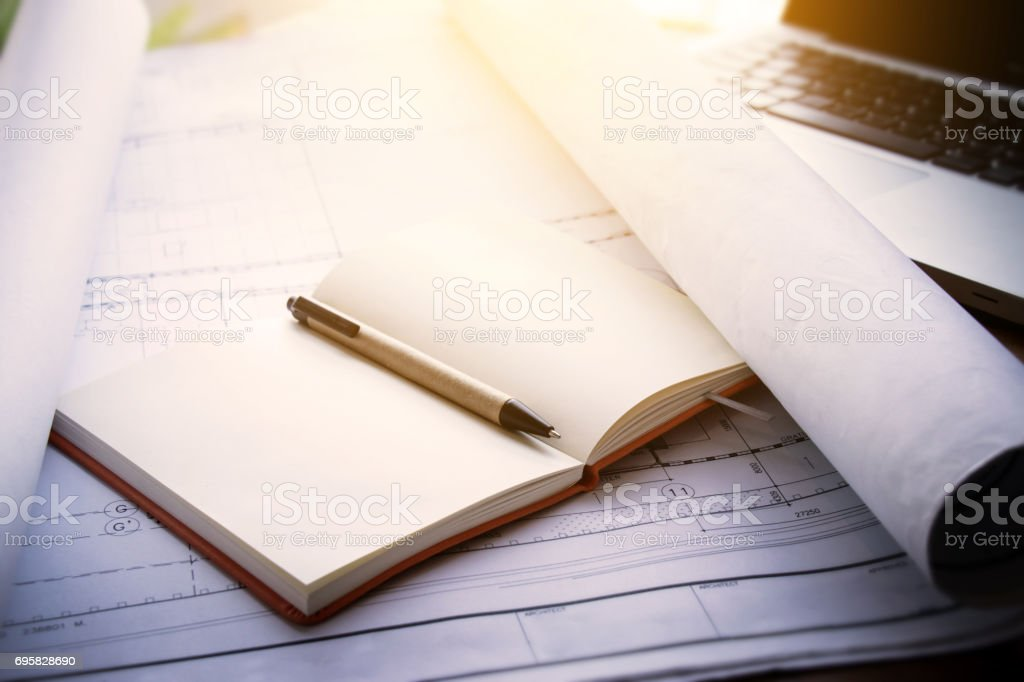 architect workplace background : notebook on blueprints for architectural plan with laptop on table in architect man working office, Vintage light effect. stock photo
