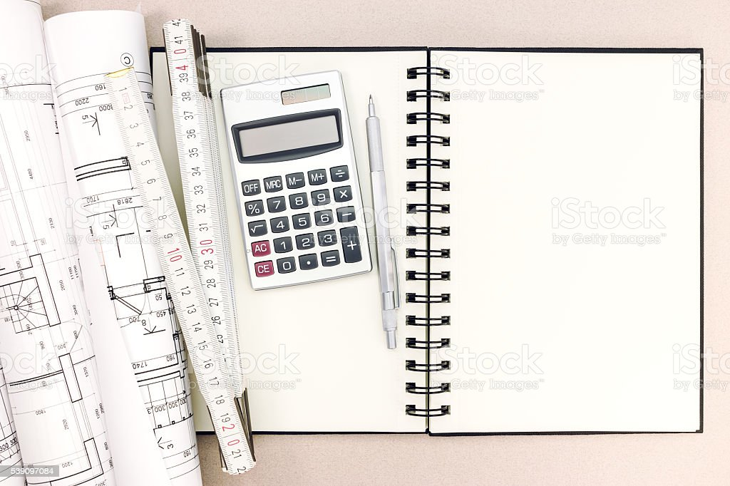 architect workspace with blueprints, notepad, folding rule and calculator stock photo