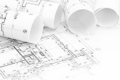 architect workspace with rolls of blueprints and technical drawing