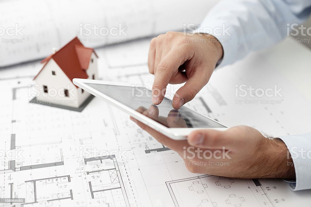 Architect zooming in on a tablet over a blueprint royalty-free stock photo