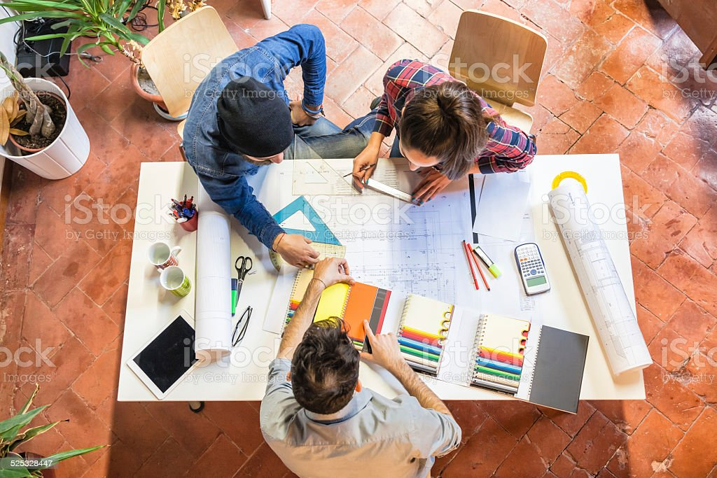 Architects at work studying a blueprint stock photo