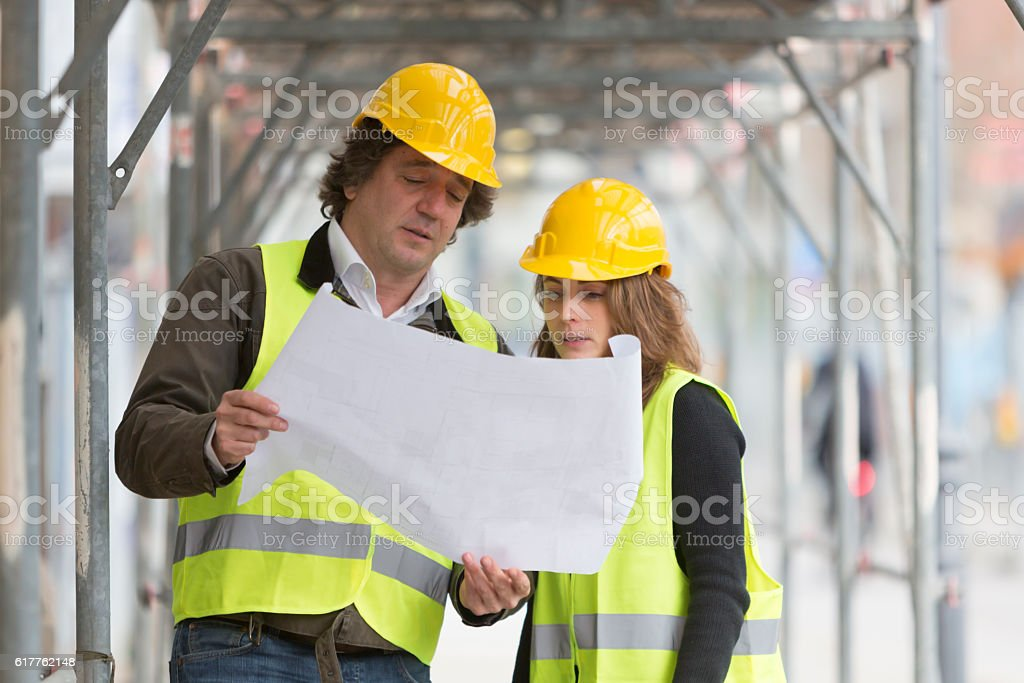 Architects checking blueprints among scaffolding on construction site stock photo