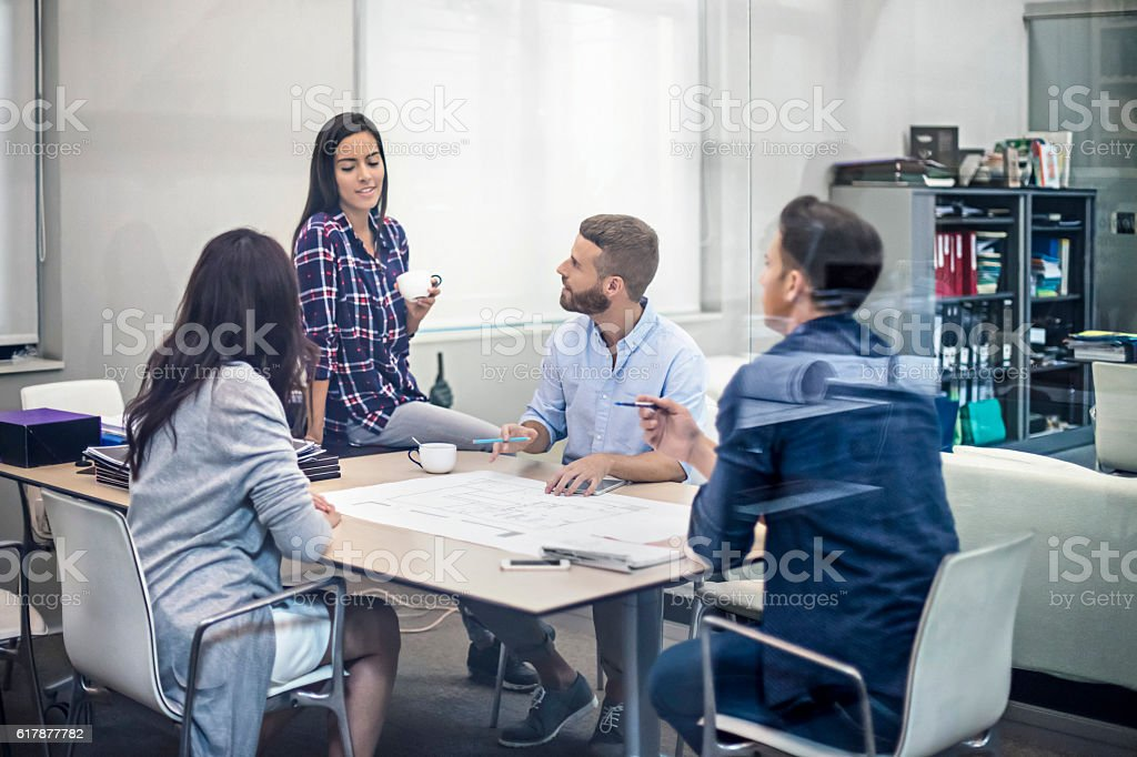 Architects discussing blueprints around a table stock photo