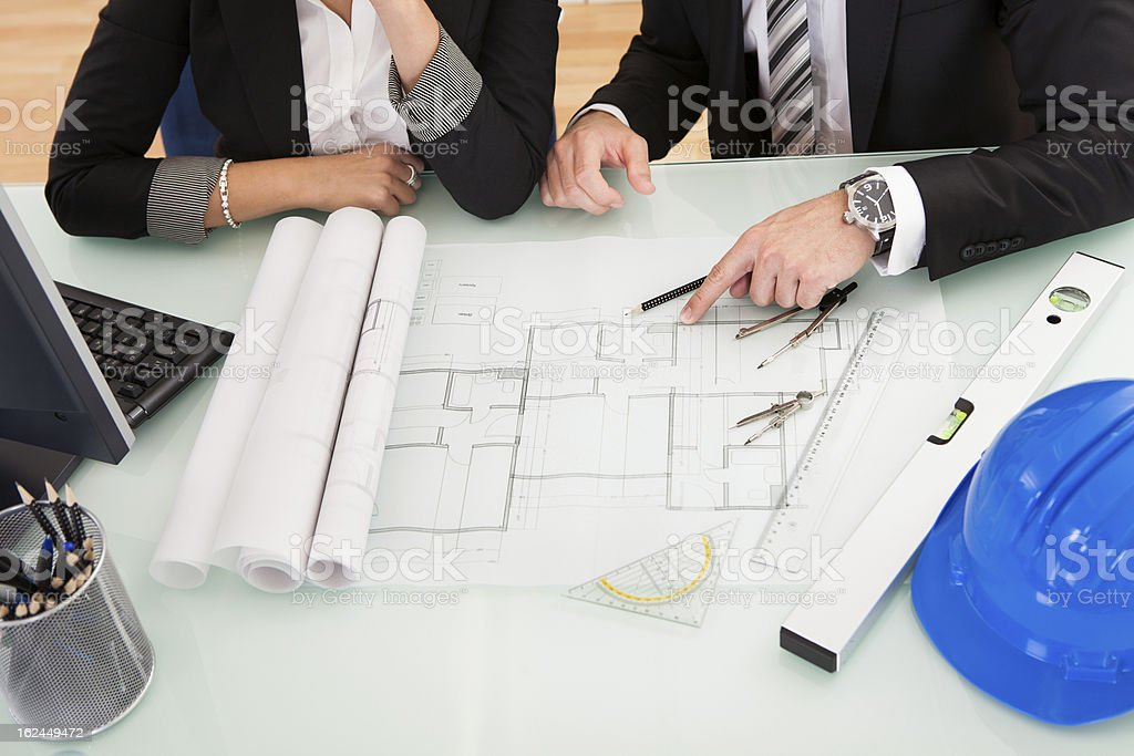 Architects discussing blueprints royalty-free stock photo