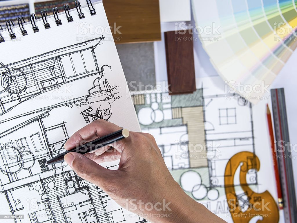 Architect's hands drawing home illustration with material sample, renovation  concept stock photo