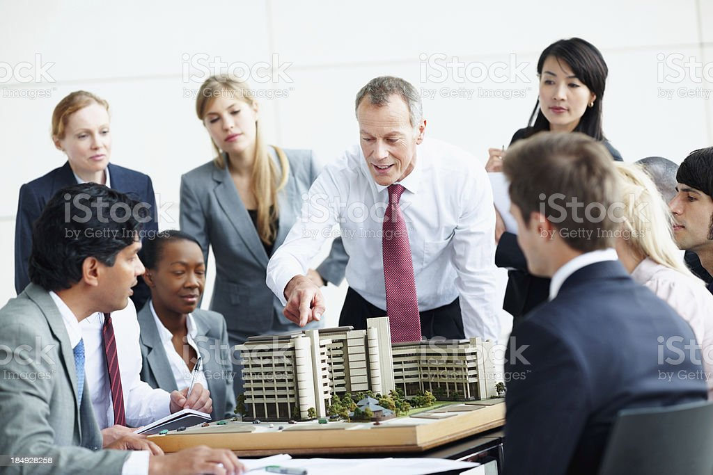 Architects in discussion about building model royalty-free stock photo