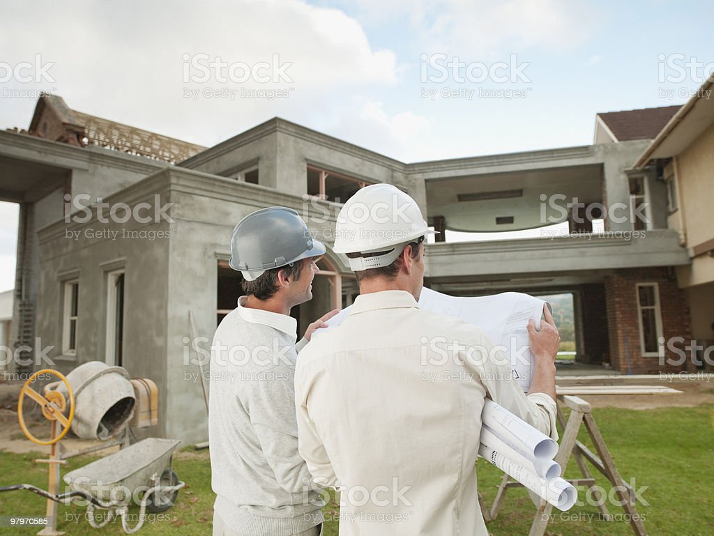 Architects in hard-hats holding blueprints and looking at house under construction royalty-free stock photo