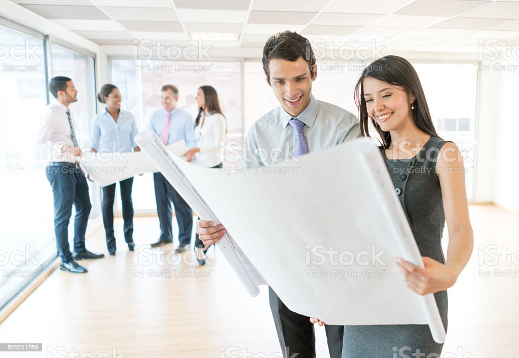 Architects looking at a blueprint stock photo