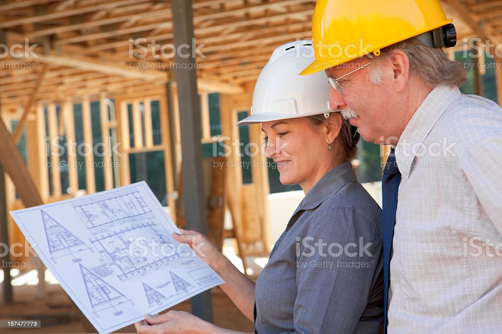 2 architects looking at a drawing on a construction site royalty-free stock photo
