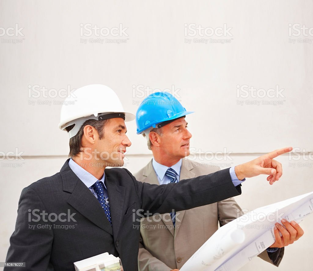 Architects onsite wearing hardhats and discussing blueprints royalty-free stock photo