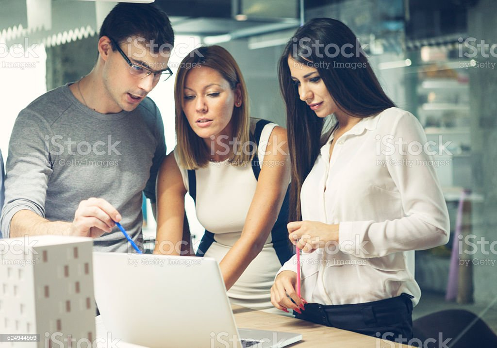 Architects reviewing architectural model in the office. stock photo