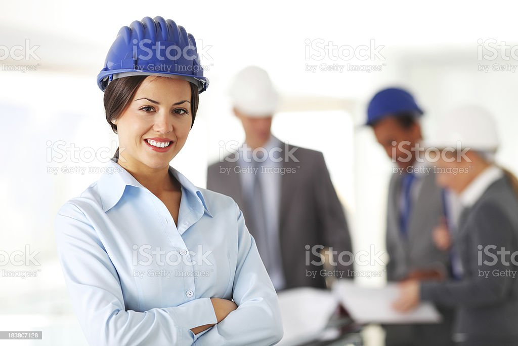 Architects reviewing blueprints. In the foreground smiling woman royalty-free stock photo