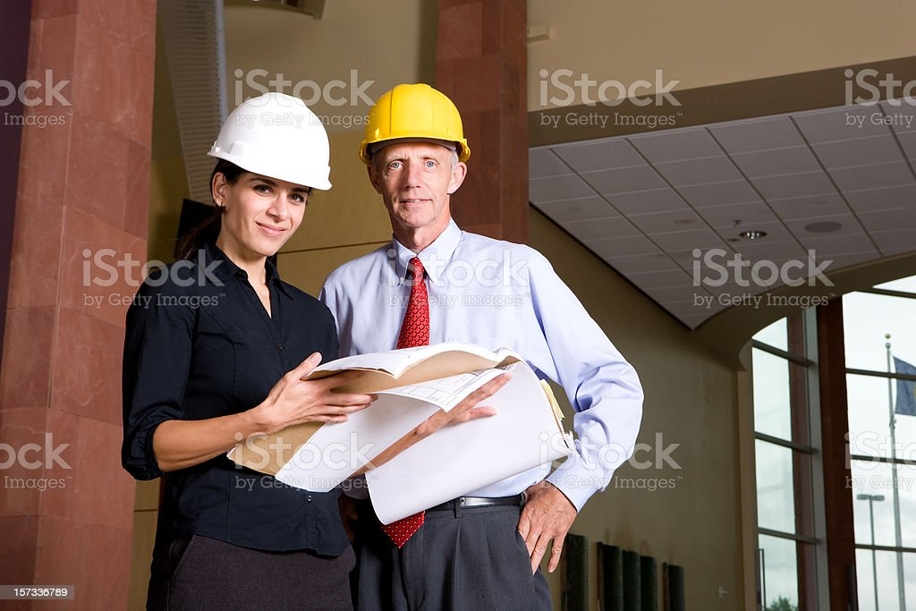 Architects Reviewing Blueprints On Site royalty-free stock photo