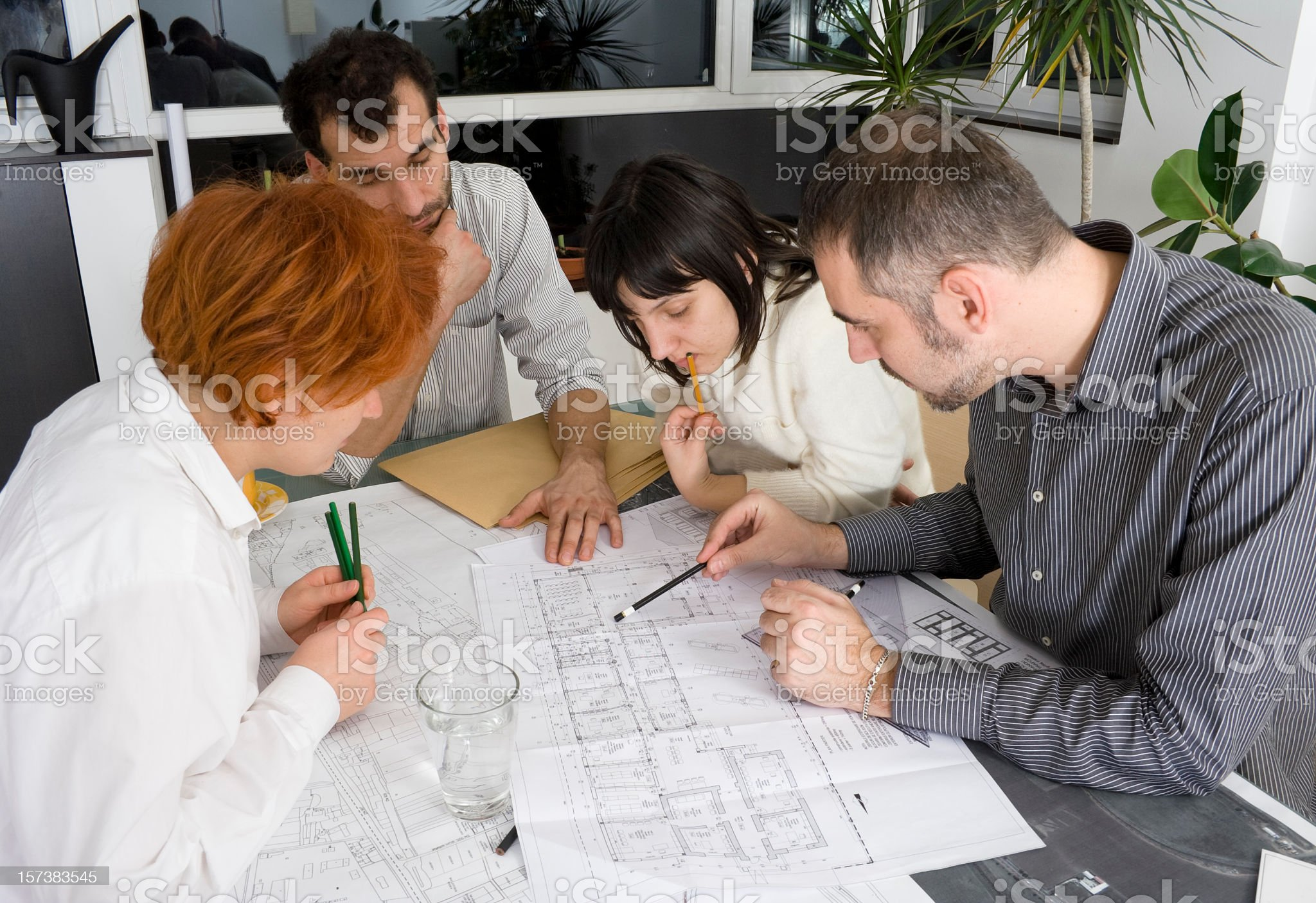 Architects sitting together working on a blue print royalty-free stock photo