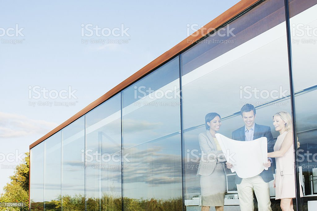 Architects with blueprint in office window royalty-free stock photo