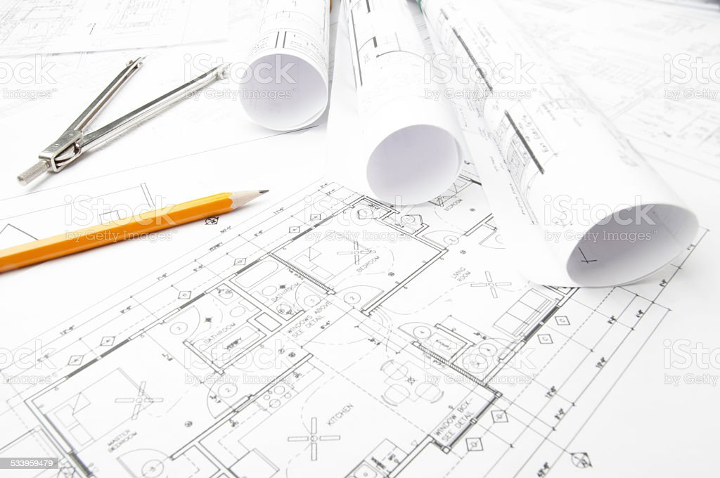 Architectural blueprints and blueprint rolls with drawing instruments stock photo