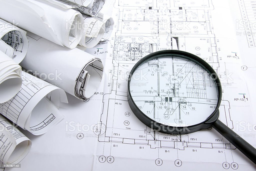 Architectural blueprints and blueprint rolls with magnifying glass stock photo