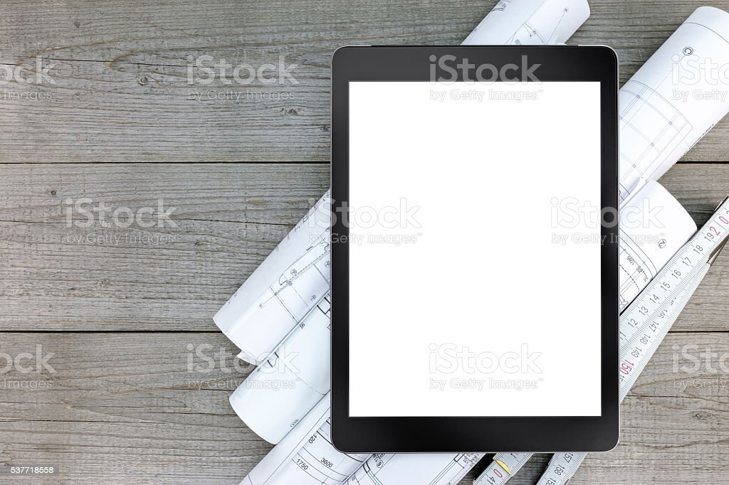 architectural blueprints with blank tablet on gray wooden boards stock photo