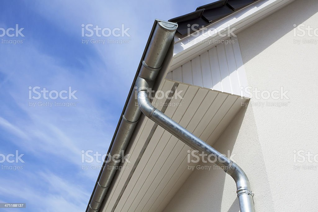 Architectural close-up of a metal rain gutter with downspout stock photo