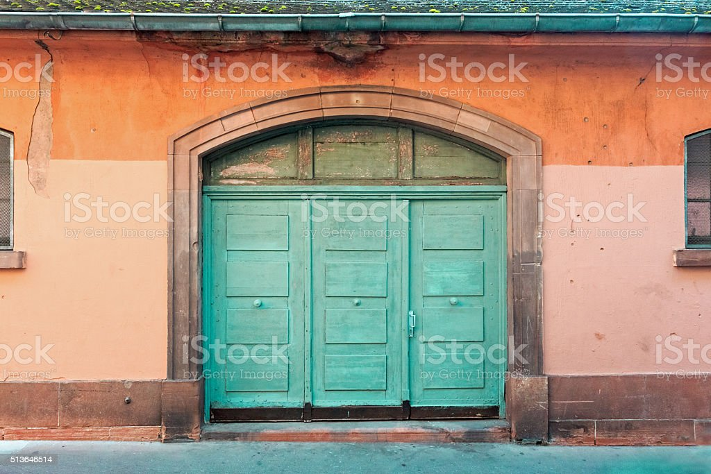 Architectural detail in Strasbourg: Green wooden door and orange wall stock photo