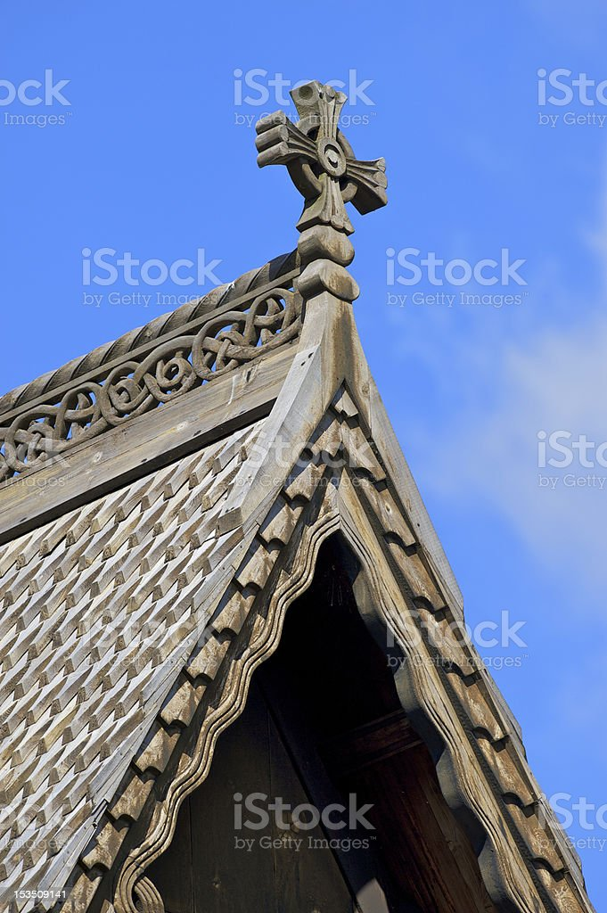 Architectural detail of Norwegian stave church roof with a cross stock photo