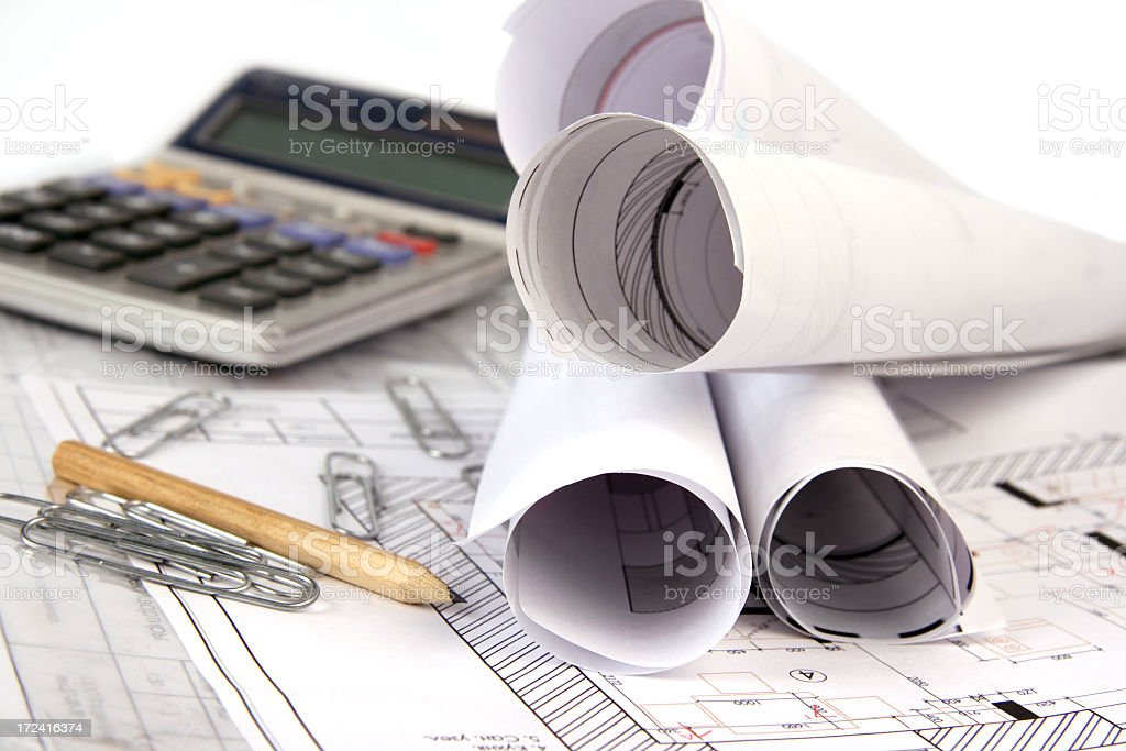Architectural drafts rolled up with drafting supplies stock photo