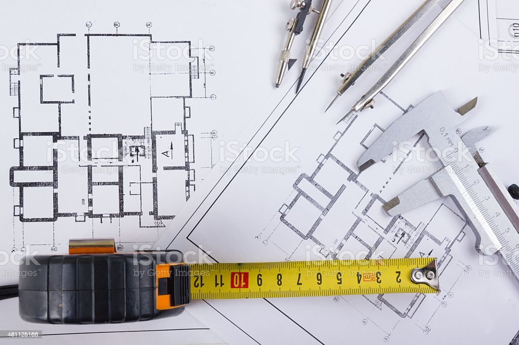 Architectural project, blueprints, divider compass, calipers, pencil, calculator on plans stock photo