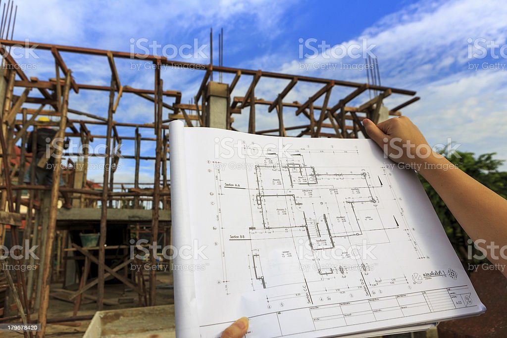 architecture drawings in hand on house building background with royalty-free stock photo