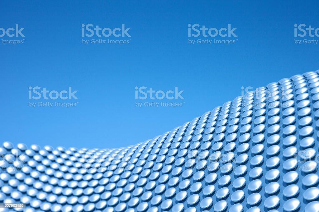 Architecture geometric background, waving metal pattern on blue sky stock photo
