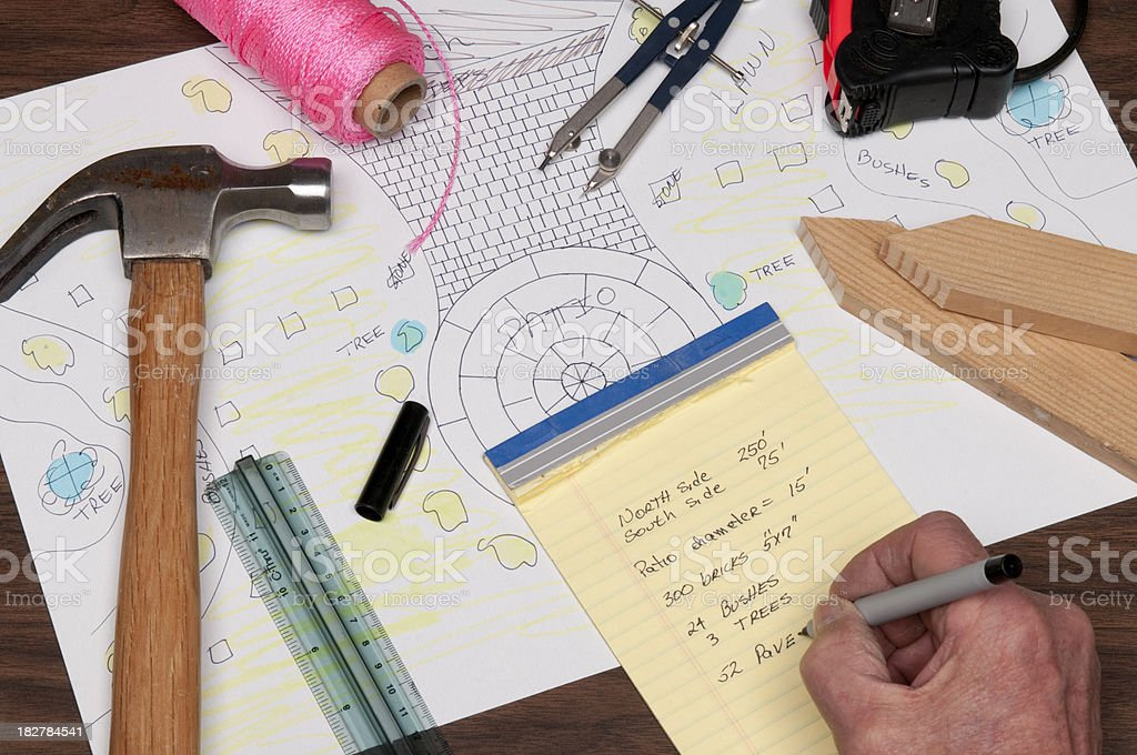 Architecture planning items laid out beside plans on desk. royalty-free stock photo