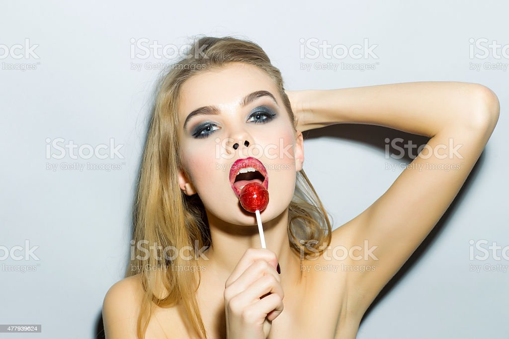 Ardent blonde girl portrait with sugar candy stock photo
