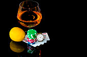 Сards with chips to play poker and snifter brandy with lemon
