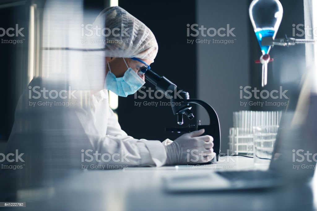 Shot of a female scientist using microscope in the lab.