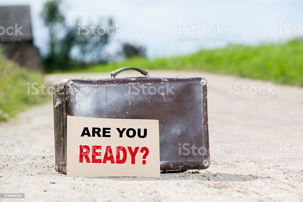 Are you Ready? Old traveling suitcase on country road stock photo