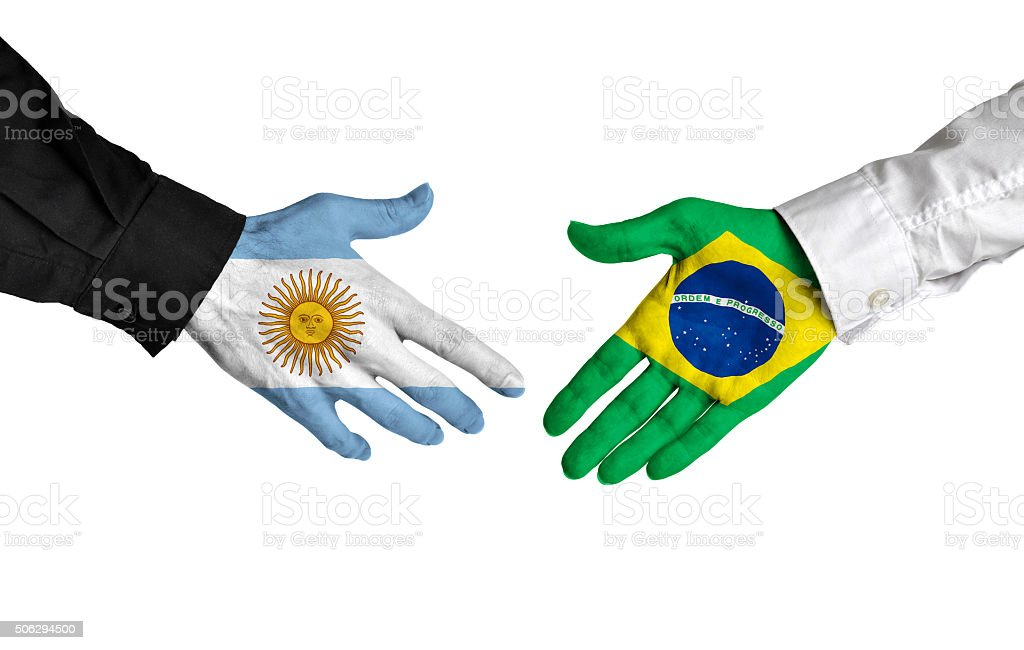 Argentina and Brazil leaders shaking hands on a deal agreement stock photo